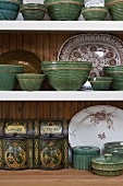 Antique crockery and an antique tin on a shelf