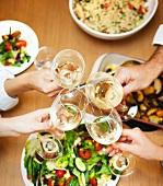 Vier Personen an gedecktem Tisch stossen mit Weingläsern an