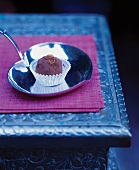 A Chocolate Truffle with Orange Zest Garnish on a Heart Shaped Metal Dish