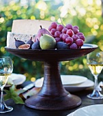 Organic Fall Fruit and Cheese on a Pedestal Dish on an Outdoor Table