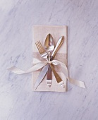 Elegant Place Setting with Fork, Knife and Spoon Tied to a Cloth Napkin with a Ribbon