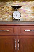 Retro-Küchenwaage auf Edelholz-Unterschrank vor changierend gefärbten Glasfliesen