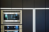 Microwave and oven surrounded by contemporary wooden cabinets