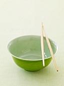 Leere grüne Essschale mit Essstäbchen