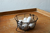 Eggs in a wire basket on a wooden tray