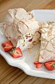 Meringue roulade with cream, strawberries and passion fruit