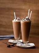 Two Chocolate Milkshakes Topped with Whipped Cream and Chocolate Shavings; With Straws