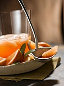 Ruby Red Grapefruit and Apple Punch in a Glass Container; Punch and Grapefruit Segment in Ladle