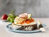 Belegtes Brot mit Frischkäse, Räucherlachs, Gurken und Radieschen