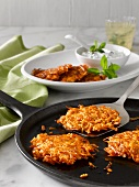 Sweet Potato Cakes on Cast Iron Skillet; Spatula Lifting One; Potato Cakes on Platter with Yogurt Sauce