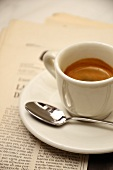 Espressotasse mit Löffel auf Zeitung