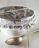 A pudding basin covered with aluminium foil