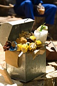 A box containing chargrilled vegetable skewers, breaded chicken drumsticks, peanuts and a sandwich