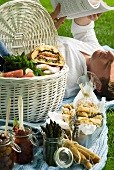 A full picnic basket next to a man lying on the picnic blanket reading a book