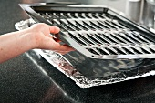 Placing a Broiler Pan on a Foil Lined Pan