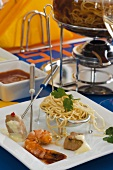 Fondue with prawns, tuna and egg noodles