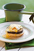 One half of a roll topped with a slice of aubergine and a poached egg