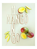 Fresh mangos next to lettering