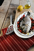 Oven roasted porgy wrapped in foil with cherry tomatoes and olives