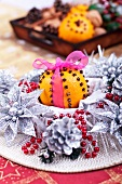 An orange pierced with cloves amongst silver Christmas decorations