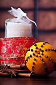 An orange pierced with cloves, spices, red and gold ribbon and a candle
