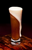 Glass Mug of Beer with Foam Spilling Over