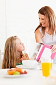 Mother pouring cereal for daughter