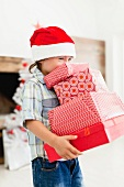 Kleiner Junge trägt einen Stapel Weihnachtsgeschenke