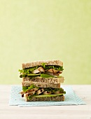 Grilled Chicken Sandwich with Lettuce and Apple Slices on Wheat Bread; Halved and Stacked