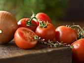 Vine Ripened Tomatoes on a Wooden Board with an Onion and Fresh Thyme