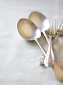 Silver cutlery on a white tablecloth