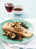 Salmon Fillet with Mushrooms Over Wild Rice; Glass of Wine and Bowl of Sauce
