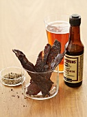 Beef Jerky with a Bottle of Worcestershire Sauce, Glass of Beer and Cracked Pepper