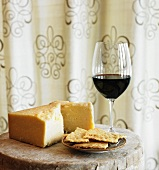 Cheddar Cheese, Crackers and a Glass of Red Wine on a Small Table