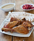 Sliced Turkey on a Platter with Drumsticks; Gravy and Cranberry Sauce
