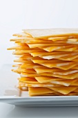 Stack of yellow American and Colby jack cheese on a white plate