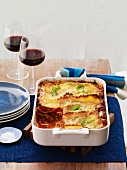 Meat Lasagna in a Baking Dish with Slice Removed; Glasses of Red Wine
