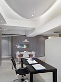 Bürodrehstuhl am schwarzen Arbeitstisch im offenen Wohnraum mit modernem Deckeneinbau und Strahlern