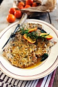 Breaded pork chops with an orange and rosemary sauce