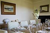 Schlicht aber festlich gedeckter Tisch und hell karierte Polsterstühle in traditionellem Esszimmer mit Kamin und Landschaftsmalerei über Anrichte.