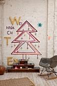 Bauhaus Schaukelstuhl vor Wand mit skizziertem Weihnachtsbaum in rustikalem Ambiente