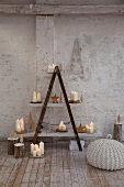 Selbstgebautes Regal mit brennenden Kerzen auf weissen Regalböden in rustikalem Ambiente