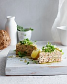 Slices of salmon crepe cake on board