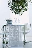 Tellerstapel und Tischläufer auf modernem Tisch unter Misteln von Decke abgehängt