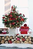 Geschmückter Weihnachtsbaum mit roten Kugeln und Geschenke auf weisser Ablage über geschichteten Holzscheiten