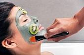 Junger Frau wird eine Gesichtsmaske mit Kiwi aufgetragen