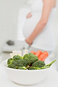 Pregnant woman with bowl of vegetables