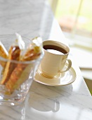 A Cup of Black Coffee with Packaged Biscotti