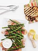 Plates of ham, asparagus, and bread