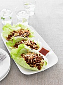Hoisin pork with bean sprouts and peanuts in lettuce leaves